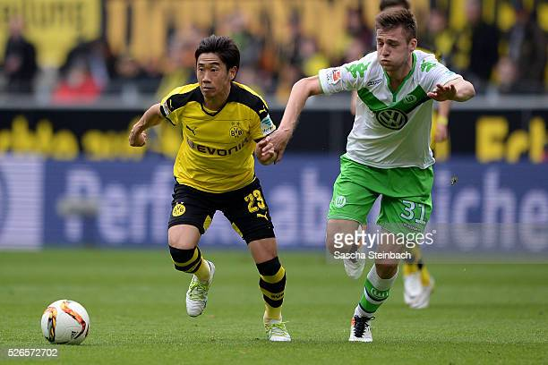 Shinji Kagawa of Dortmund goes past Robin Knoche of Wolfsburg during the Bundesliga match between Borussia Dortmund and VfL Wolfsburg at Signal Iduna...