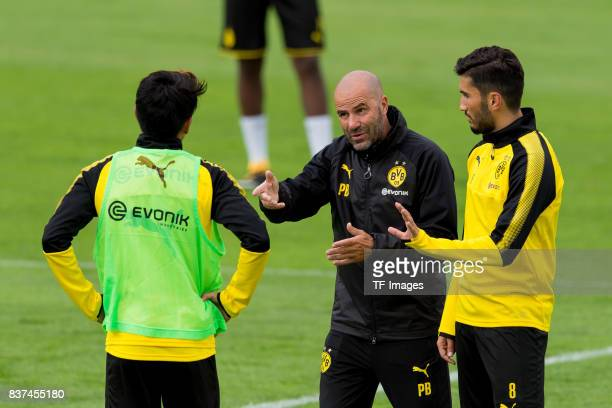 Shinji Kagawa of Dortmund Head coach Peter Bosz of Dortmund speak with Nuri Sahin of Dortmund during a training session as part of the training camp...