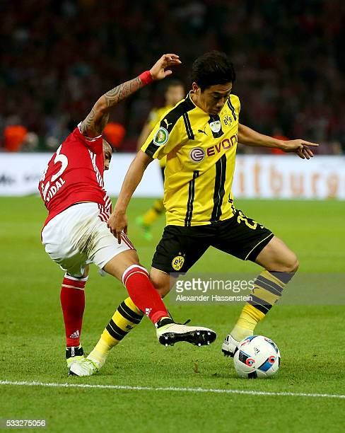 Shinji Kagawa of Dortmund is challenged by Arturo Vidal of Muenchen during the DFB Cup Final 2016 between Bayern Muenchen and Borussia Dortmund at...