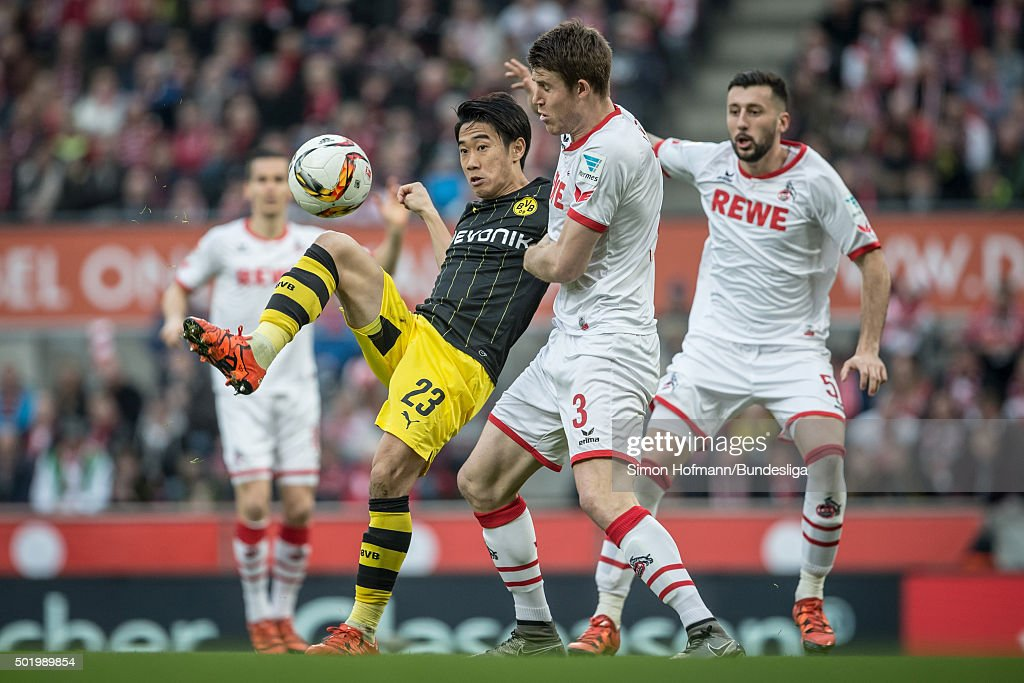 Shinji Kagawa of Dortmund is challenged by Dominique Heintz of Koeln during the Bundesliga match between 1. FC Koeln and Borussia Dortmund at RheinEnergieStadion on December 19, 2015 in Cologne, Germany.