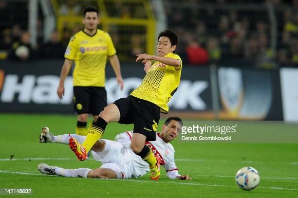 Shinji Kagawa of Dortmund is challenged by Vedad Ibisevic of Stuttgart during the Bundesliga match between Borussia Dortmund and VfB Stuttgart at...
