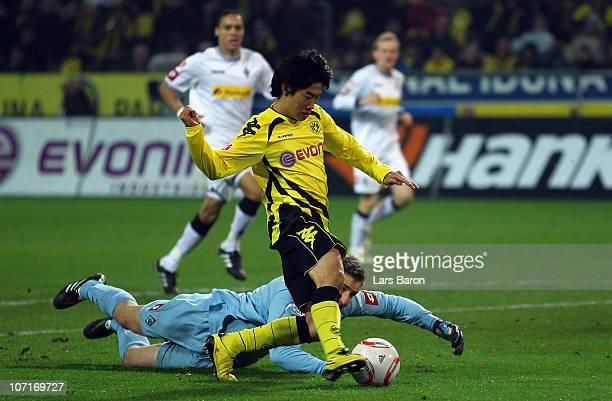 Shinji Kagawa of Dortmund scores the first goal past goalkeeper Christofer Heimeroth of Moenchengladbach during the Bundesliga match between Borussia...