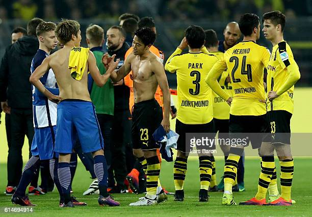 Shinji Kagawa of Dortmund shake hand with Genki Haraguchi of Berlin battle for the ball during the Bundesliga match between Borussia Dortmund and...