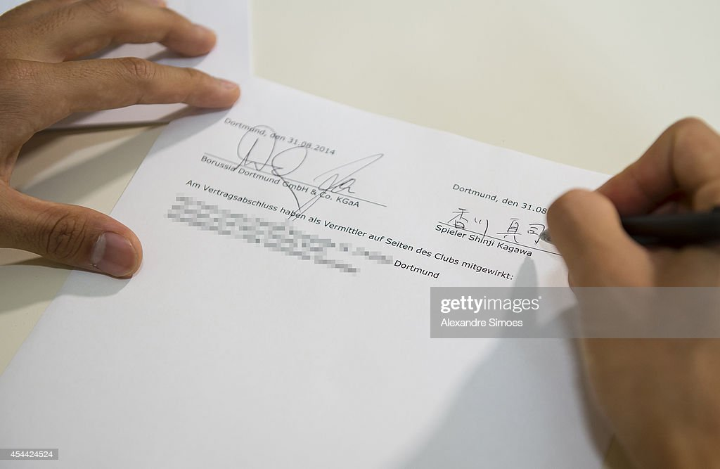 Parts of this image have been obscured in accordance with Germany's privacy laws.) Shinji Kagawa of Dortmund signs his new Borussia Dortmund contract at Dortmund on August 31, 2014 in Dortmund, Germany.