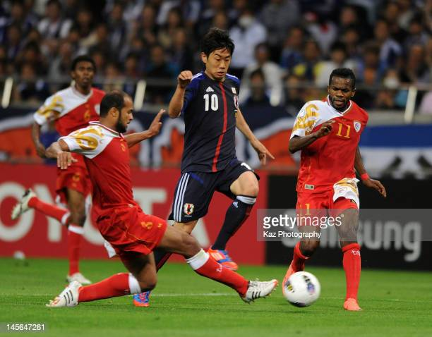 Shinji Kagawa of Japan competes for the ball against Jaber Mohammed Saghayar Al Owaisi and Abdul Sallam Amur Juma Al Mukhaini of Oman during the FIFA...