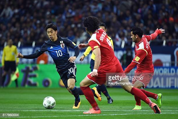 Shinji Kagawa of Japan competes for the ball against Mhd Zahir Algunami Almedani and Hamdi Al Massri of Syria during the FIFA World Cup Russia Asian...