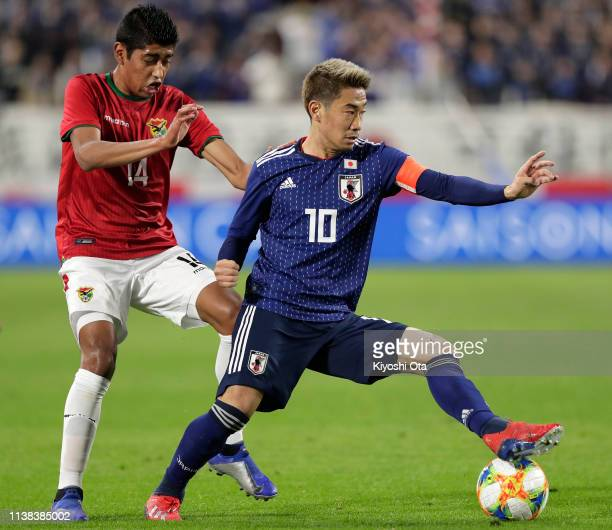 Shinji Kagawa of Japan in action against Raul Castro of Bolivia during the international friendly match between Japan and Bolivia at Noevir Stadium...