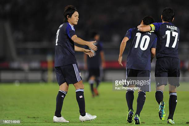 Shinji Kagawa of Japan is celebrated by his team mates Yasuhito Endo and Makoto Hasebe of Japan after scoring Japan's first goal during the...