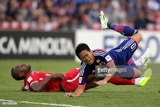 Shinji Kagawa of Japan is tackled by Abdallah Jaber of Palestine during the 2015 Asian Cup match between Japan and Palestine at Hunter Stadium on...