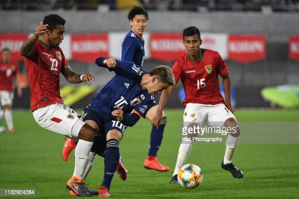 Shinji Kagawa of Japan lost the ball under the challenge from Adrian Jusino of Bolivia during the international friendly match between Japan and...