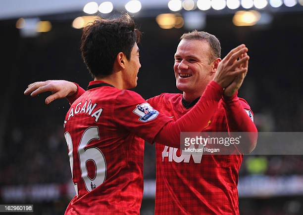 Shinji Kagawa of Manchester United celebrates scoring to make it 3-0 with team mate and claim a hat-trick with team mate Wayne Rooney during the...