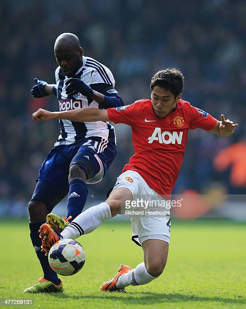Shinji Kagawa of Manchester United tackles Youssuf Mulumbu of West Bromwich Albion during the Barclays Premier League match between West Bromwich...