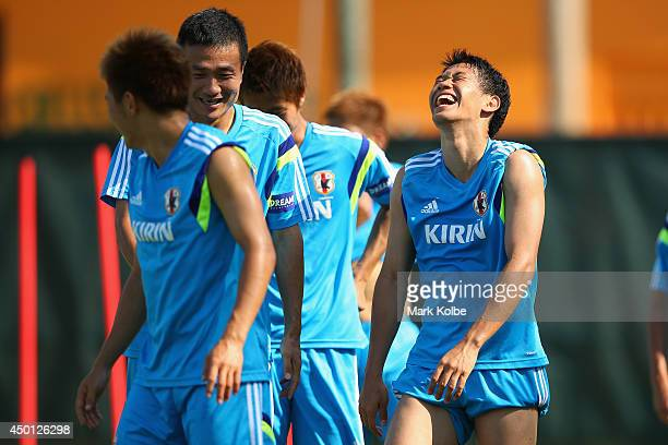 Shinji Kagawa shares a laugh with a team mate during a Japan training session at North Greenwood Recreation Aquatic Complex on June 5 2014 in...