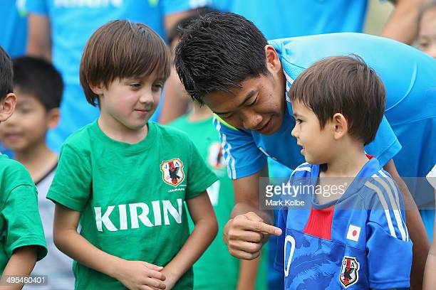 Shinji Kagawa speaks to a local boy as he waits with the Japan squad to pose for pictures with children from the local area during a Japan training...