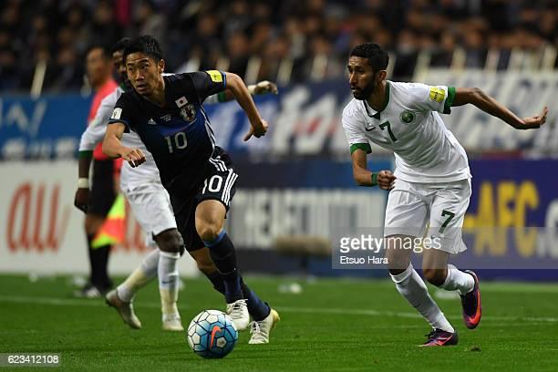 Shinji Kagawa#10 of Japan and Salman Alfaraj#7 of Saudi Arabia compete for the ball during the 2018 FIFA World Cup Qualifier match between Japan and...