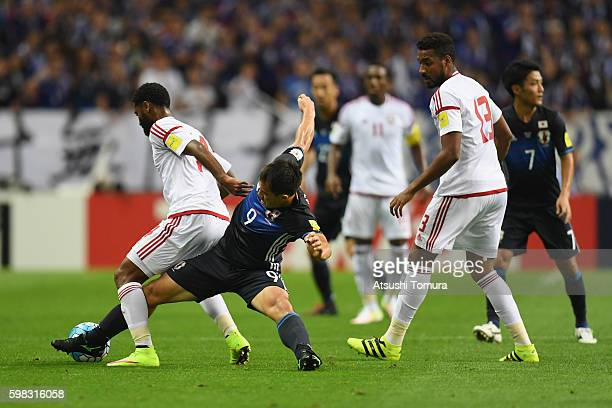 Shinji Okazaki of Japan Abdelaziz Sanqour of the United Arab Emirates compete for the ball during the 2018 FIFA World Cup Qualifier Final Round Group...