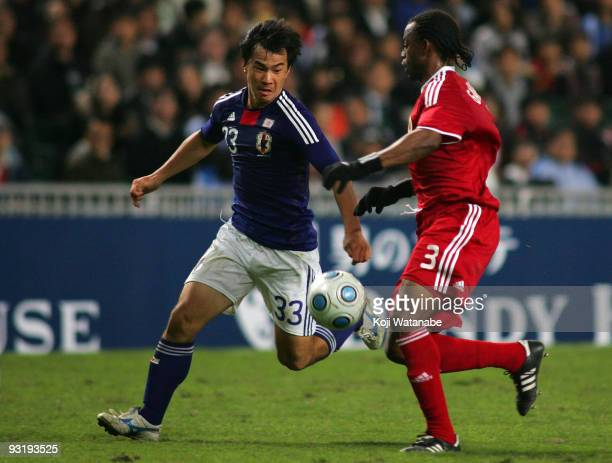 Shinji Okazaki of Japan and Gerard Ambassa Guy of Hong Kong compete for the ball during AFC Asia Cup 2011 Qatar qualifier match between Hong Kong and...
