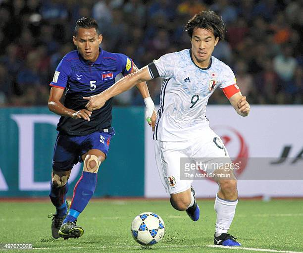 Shinji Okazaki of Japan and Soeuy Visal of Cambodia compete for the ball during the 2018 FIFA World Cup Qualifier match between Cambodia and Japan at...