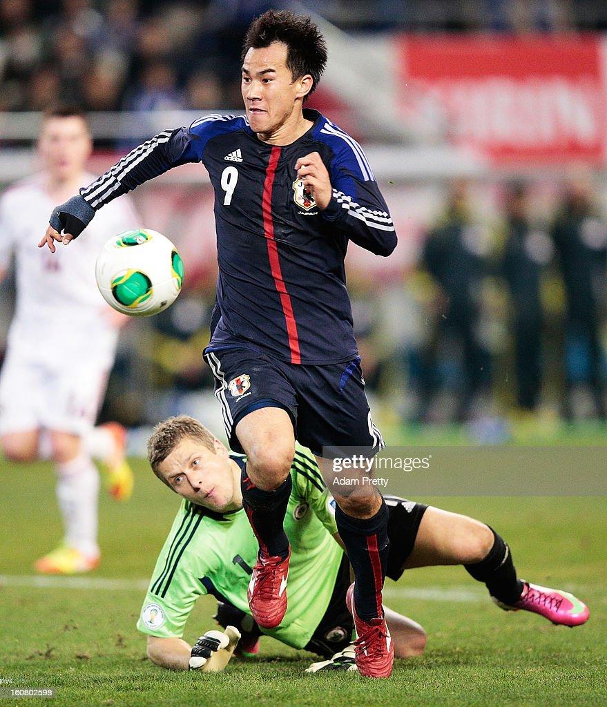 Shinji Okazaki of Japan beats the Latvian Goalkeeper to score his second goal during the international friendly match between Japan and Latvia at Home's Stadium Kobe on February 6, 2013 in Kobe, Japan.