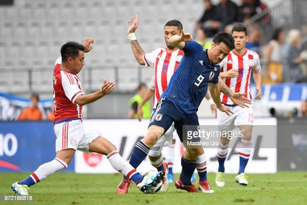 Shinji Okazaki of Japan controls the ball under pressure of Paraguay defense during the international friendly match between Japan and Paraguay at...