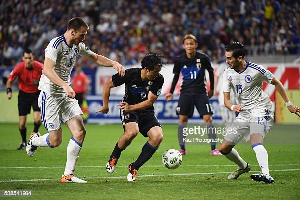 Shinji Okazaki of Japan controls the ball under pressure of Toni Sunjic and Mario Vrancic of Bosnia and Herzegovina during the international friendly...