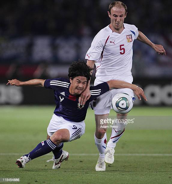 Shinji Okazaki of Japan is challenged by Roman Hubnik of the Czech Republic during the Kirin Cup Soccer match between Japan and the Czech Republic...