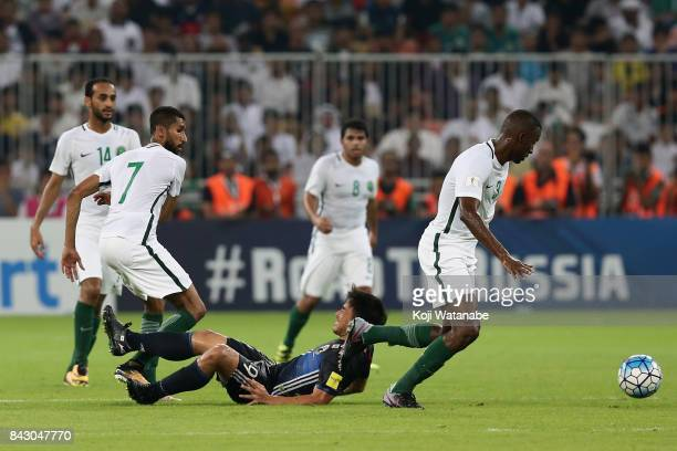 Shinji Okazaki of Japan is challenged by Saudi Arbia defense uring the FIFA World Cup qualifier match between Saudi Arabia and Japan at the King...