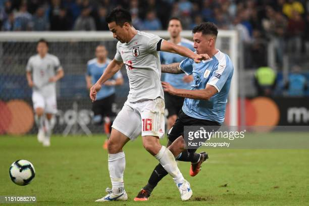 Shinji Okazaki of Japan keeps the ball under the pressure of Jose Maria Gimenez of Uruguay during the Copa America Brazil 2019 group C match between...