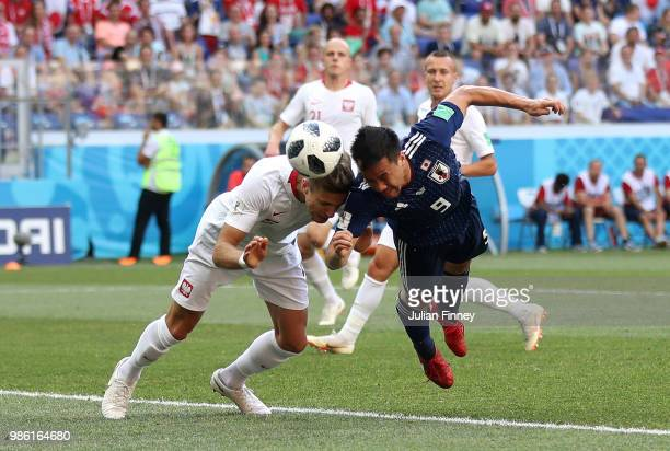 Shinji Okazaki of Japan win a header over Jan Bednarek of Poland during the 2018 FIFA World Cup Russia group H match between Japan and Poland at...