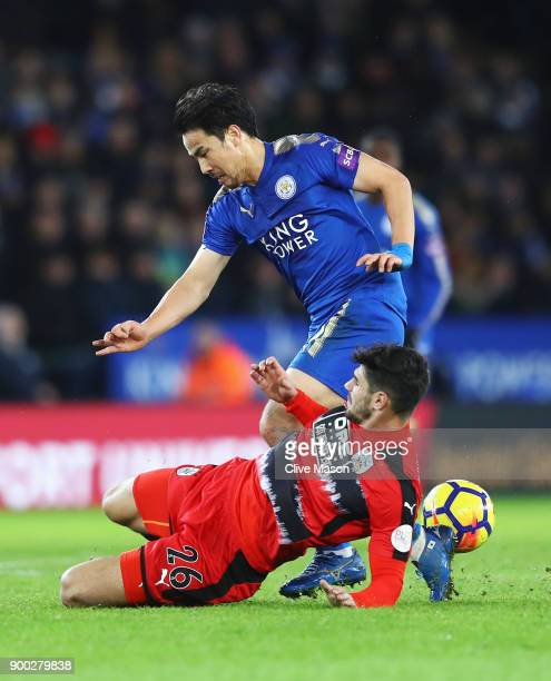 Shinji Okazaki of Leicester City is tackled by Christopher Schindler of Huddersfield Town during the Premier League match between Leicester City and...