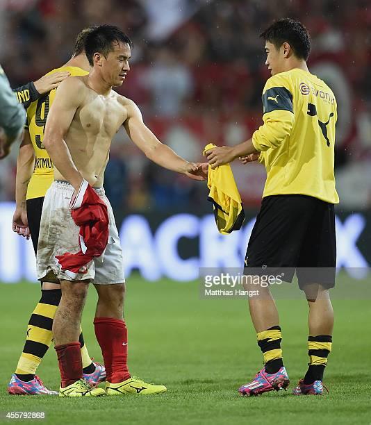 Shinji Okazaki of Mainz and Shinji Kagawa of Dortmund change jerseys after the Bundesliga match between 1 FSV Mainz 05 and Borussia Dortmund at...