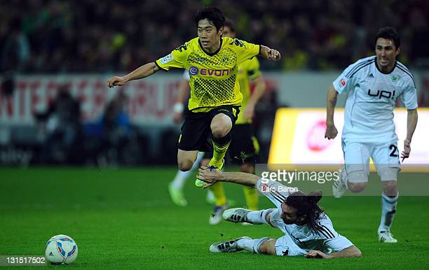 Shinjie Kagawa of Dortmund is challenged by Sotirios Kyrgiakos of Wolfsburg during the Bundesliga match between Borussia Dortmund and VfL Wolfsburg...