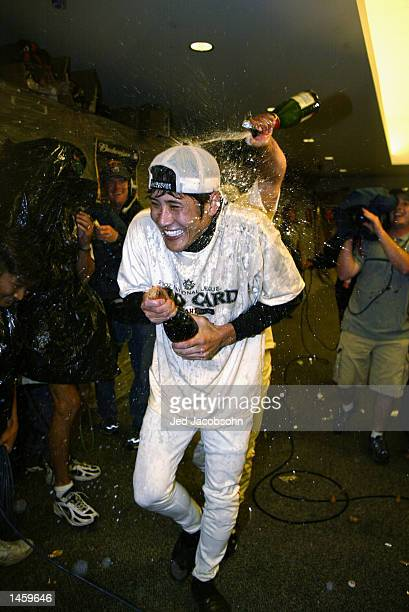 Shinjo Tsuyoshi of the San Francisco Giants is doused by champagne by teammates after beating the Houston Astros to win the National League wild card...