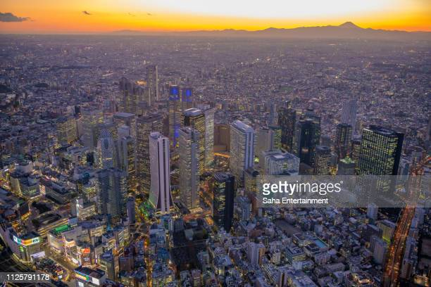 shinjuku buildings light up aerial at dusk - saha entertainment stock pictures, royalty-free photos & images