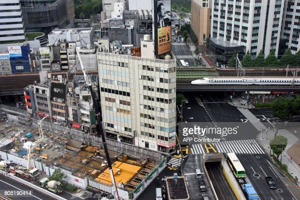 A Shinkansen bullet train crosses over a street beside a construction site in Tokyo on July 1 2017 Tokyo will hold a local election on July 2 / AFP...