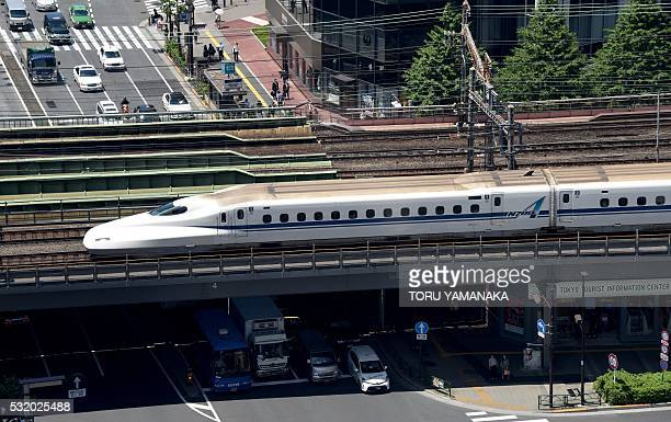 A Shinkansen bullet train goes over a street in Tokyo on May 18 2016 Japan sidestepped a recession with modest firstquarter growth preliminary data...