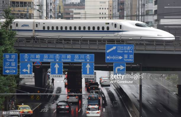 A Shinkansen bullet train moves on tracks above traffic in Tokyo on August 14 2017 Japan's economy grew 10 percent in the AprilJune period notching...