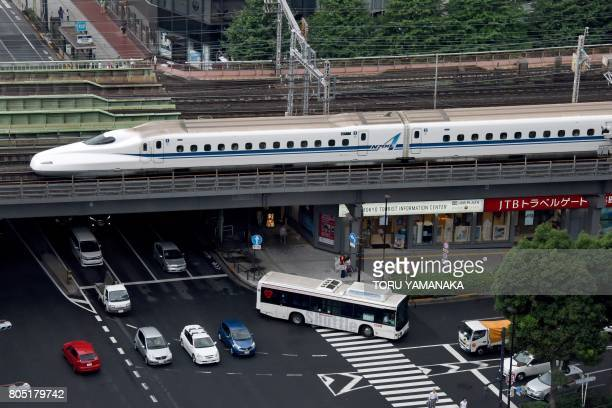 A Shinkansen bullet train passes over a street in Tokyo on July 1 2017 Tokyo will hold a local election on July 2 / AFP PHOTO / Toru YAMANAKA