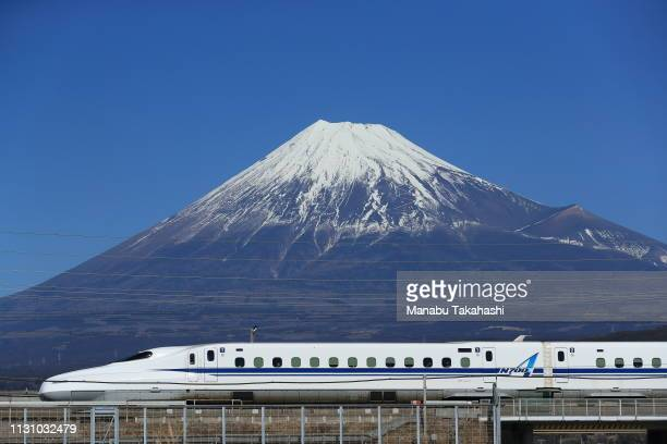 Shinkansen bullet train runs in front of Mt Fuji between Mishima and ShinFuji stations on February 3 2017 in Fuji Shizuoka Japan