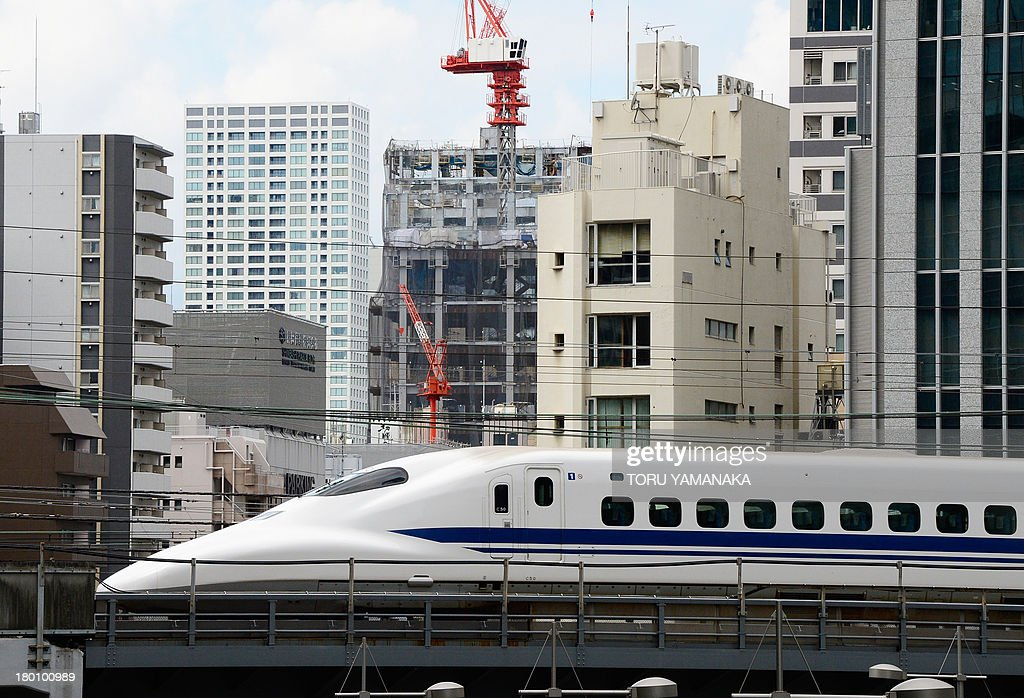 A 'shinkansen' or bullet train speeds amongst buildings in Tokyo on September 9, 2013. Japan's economy grew more than initially thought in the June quarter, revised data showed on September 9, supplying more evidence of an economic recovery which is likely to clear the way for a hike in the nation's sales tax. AFP PHOTO/Toru YAMANAKA