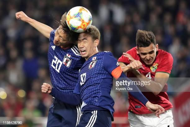 Shinnosuke Hatanaka and Shinji Kagawa of Japan in action against Luis Haquin of Bolivia during the international friendly match between Japan and...