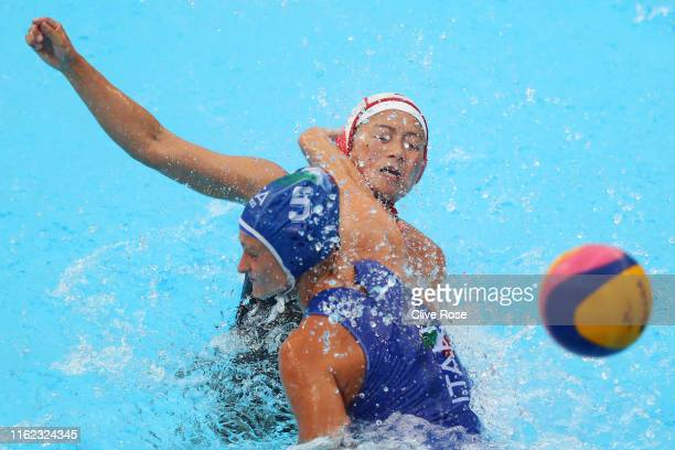 Shino Magariyama of Japan takes a shot against Rosaria Aiello of Italy during their Women's Water Polo Preliminary round match on day four of the...