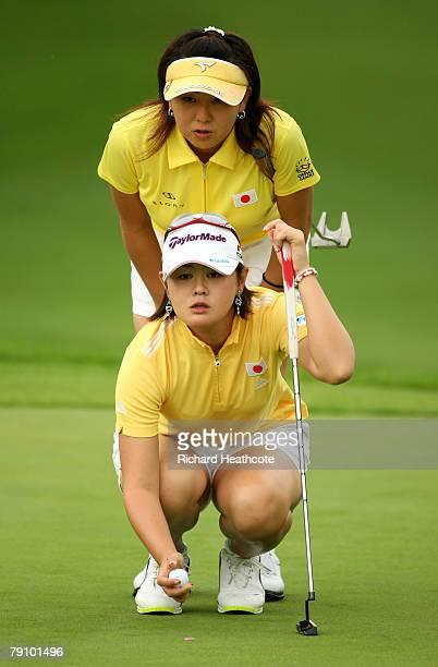 Shinobu Moromizato and Miki Saiki of Japan line up a putt on the 2nd green during the first round of the Women's World Cup of Golf at The Gary Player...