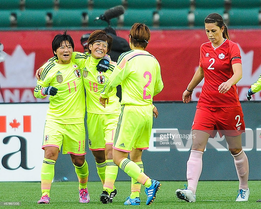 Shinobu Ohno #11, Saori Airyoshi #18, and Yukari Kinga #2 of Japan celebrate after their teammate Aya Miyama (not pictured) scored against Canada during a match at Commonwealth Stadium on October 25, 2014 in Edmonton, Alberta, Canada.
