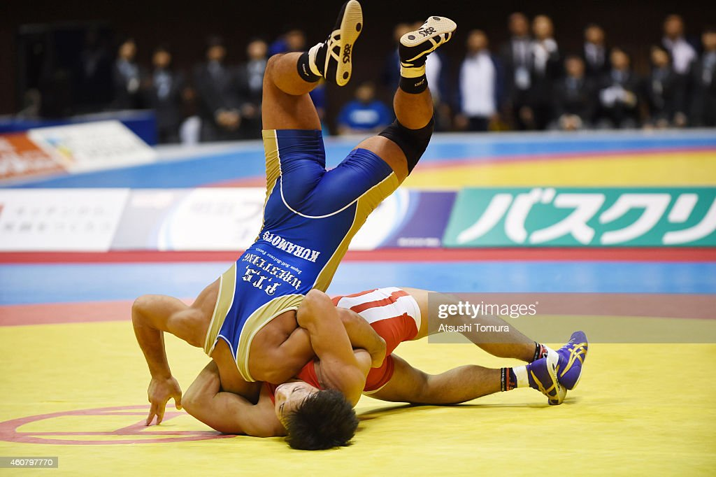 Shinobu Ota (Red) and Kazuma Kuramoto (Blue) compete in Men's 59kg Greco Roman final match during 2014 Emperor's Cup All Japan Wresting Championship on December 23, 2014 in Tokyo, Japan.