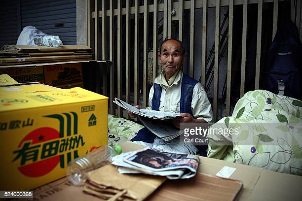 Shinpei Kirita who has lived homeless in Kamagasaki for ten years poses for a photograph behind the boxes he has piled up around his bed in the slum...