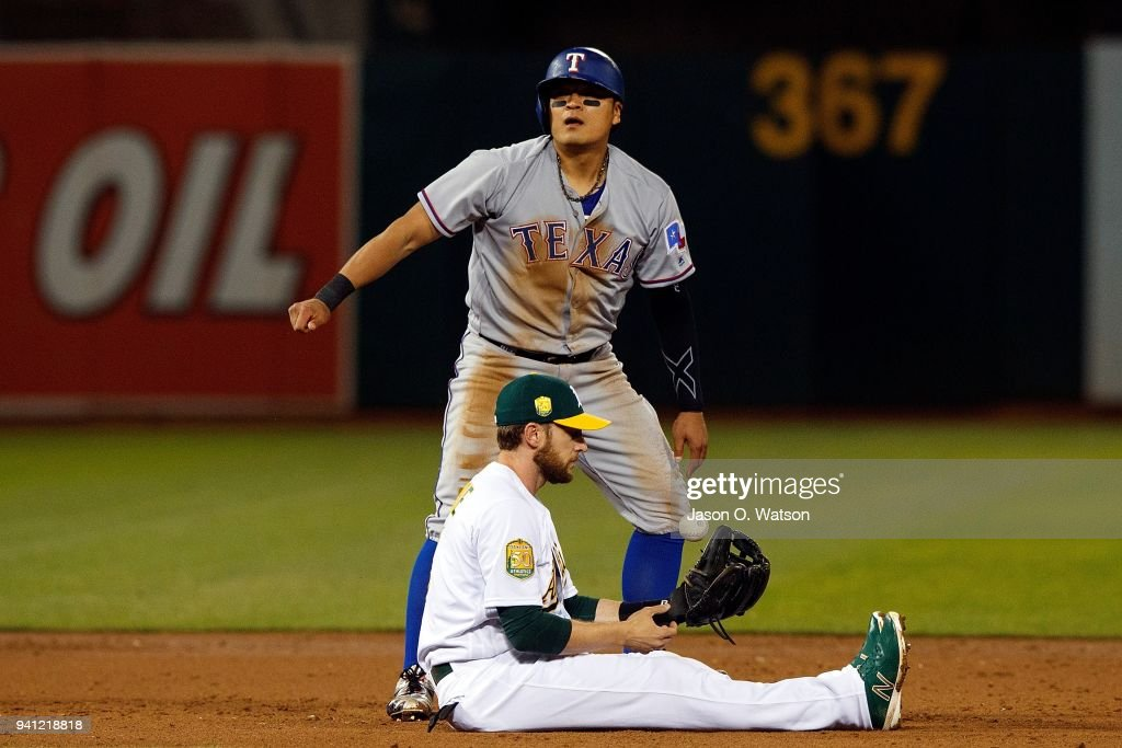 Shin-Soo Choo #17 of the Texas Rangers advances to second base after tagging up on a fly ball ahead of the throw to Jed Lowrie #8 of the Oakland Athletics during the third inning at the Oakland Coliseum on April 2, 2018 in Oakland, California. The Oakland Athletics defeated the Texas Rangers 3-1.