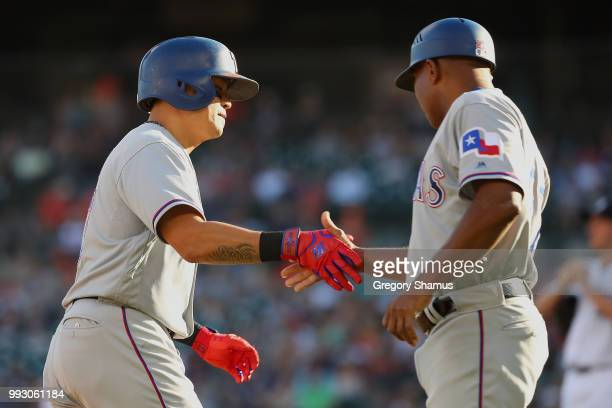 ShinSoo Choo of the Texas Rangers celebrates his first inning home run with third base coach third base coach Tony Beasley while playing the Detroit...