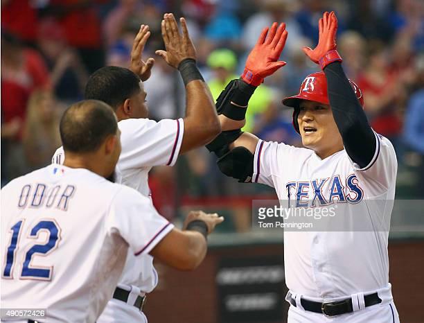 ShinSoo Choo of the Texas Rangers celebrates with Elvis Andrus of the Texas Rangers and Rougned Odor of the Texas Rangers after hitting a two run...