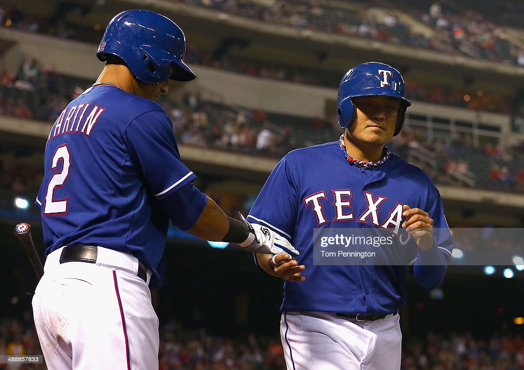 Shin-Soo Choo #17 of the Texas Rangers celebrates with Leonys Martin #2 of the Texas Rangers after scoring on a wild pitch against the Colorado Rockies at Globe Life Park in Arlington on May 8, 2014 in Arlington, Texas.